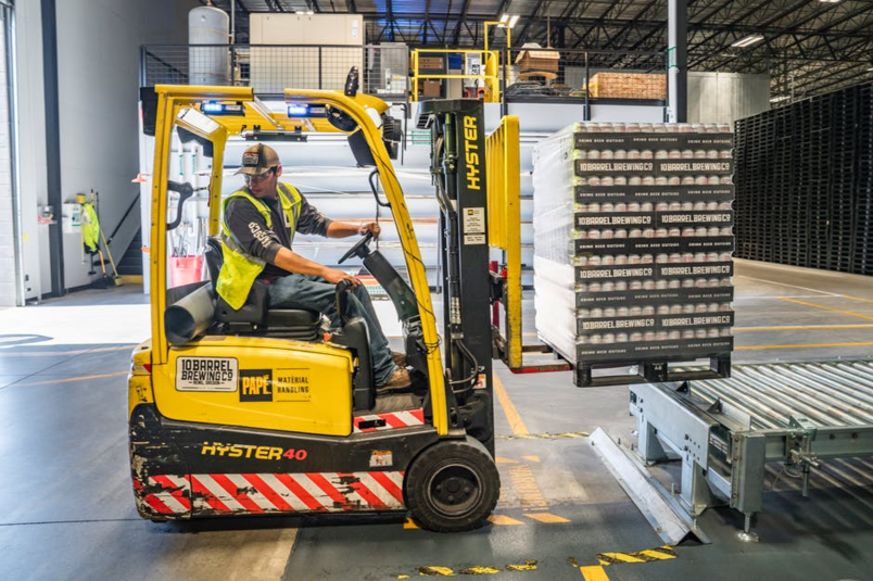 A man using a forklift to lift a pallet of goods in a warehouse