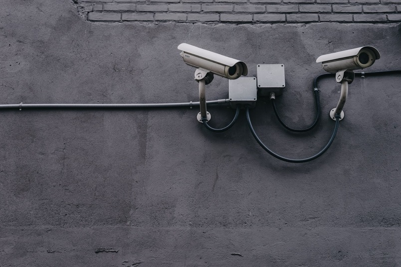 Two CCTV cameras on a grey wall