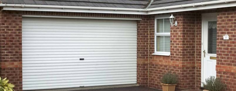 White automated roller shutter doors on the front of a garage