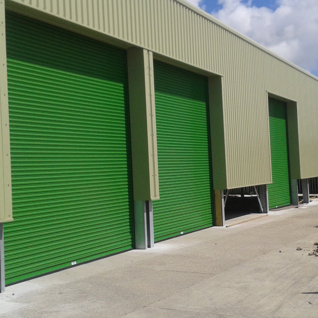 Large green industrial roller shutter doors