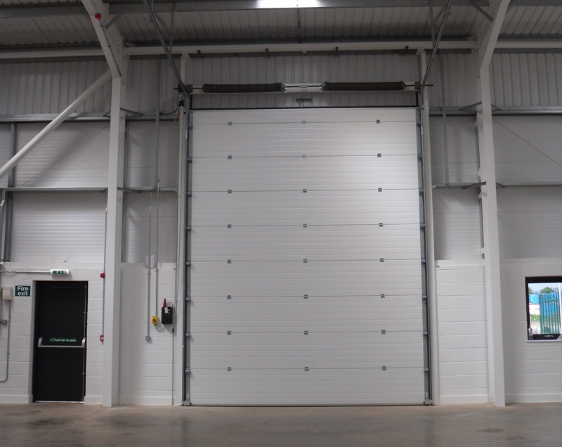 A grey panelled sectional door inside a business unit