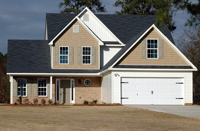 A large house with a brand new white garage door installed at the front.