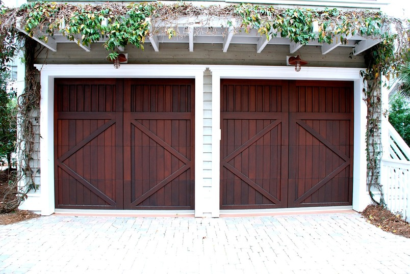 Two adjacent garage doors made from dark wood with an overhead canopy