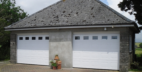 Two adjacent white sectional garage doors installed in a stone garage