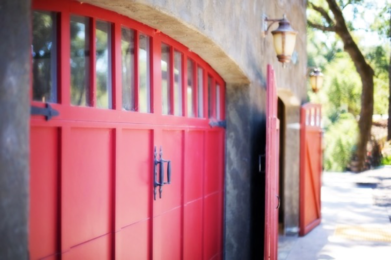 Two sets of red side hinged garage doors installed in a stone building