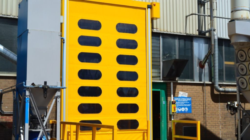 A bright yellow rapid roll door installed by Zenith Doors in an industrial estate.