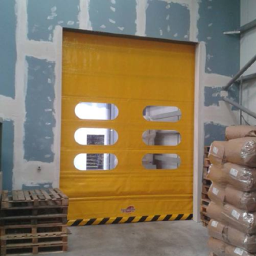 A yellow rapid roll door surrounded by wooden pallets and sandbags in a warehouse.